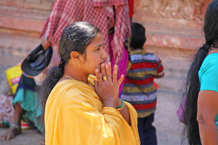 India, Hampi, 01 February 2018. An Indian woman in a bright yellow sari folded her arms in a namaste.