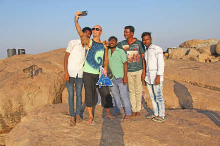 India, Hampi, January 31, 2018. Men Hindus are photographed with a European on the phone. Selfie on the phone.