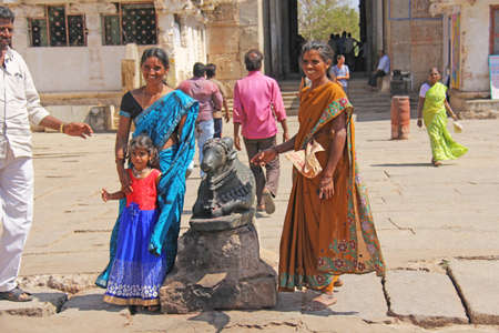 India, Hampi, 01 February 2018. Indian women and children are posing next to a figure or statue of a connected cow.