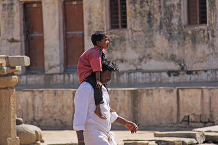 India, Hampi, 01 February 2018. A small Indian boy sits on the shoulders of the pope. Dad and son. Inside the Temple of Virupaksha.
