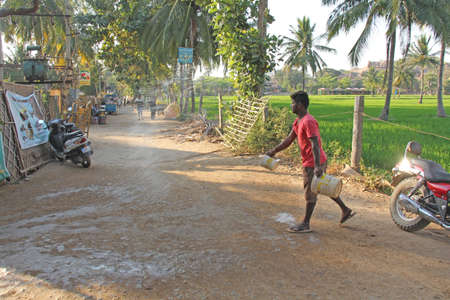 India, Hampi, 02 February 2018. The main street of the village of Virupapur Gaddi. Guesthouses overlooking the rice fields. An Indian man sprinkles water on the road. Drops of water in flight. 新聞圖片