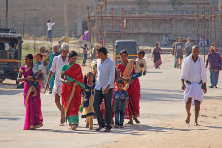 India, Hampi, 02 February 2018. The main street of Hampi village is women in bright and colorful saris, men, children, a group of people. Indian people. Motorcycle.