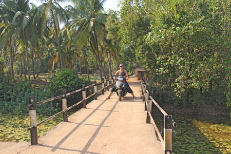 A bald young man in sunglasses sits on a black scooter, on a bridge in beautiful nature. India, Goa. Beautiful Indian landscape.
