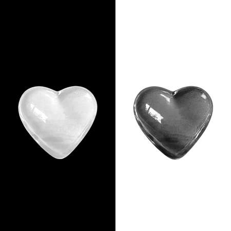 Glowing crystal white heart isolated on black background and black heart isolated on white background with clipping path. Balance of love and life concept.
