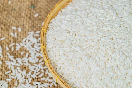 Glutinous rice in bamboo Basket with hemp sacks background Stock Photo