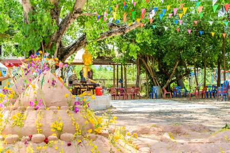 Prayer flags , pagoda and flower on sand in Songkran day festival , Thailand. Stock Photo - 78994057
