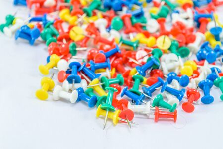Many colorful push pins isolated on a white background