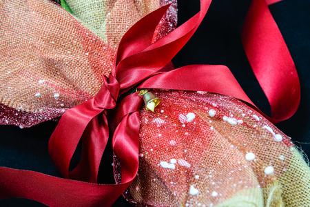 Kwiaty bukietowe z czerwoną wstążką owinięte w brązową torebkę worek