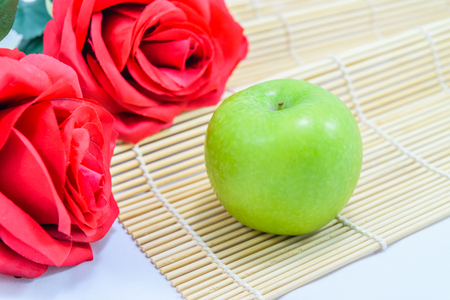 Green apples with red rose on mat Stock Photo