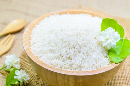 white rice (Thai Jasmine rice) with jasmine flower in wooden bowl