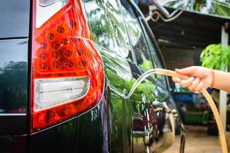 Female hand washing a black car