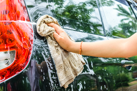 valet: Female hand washing a black car with a cloth Stock Photo