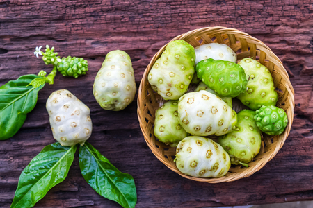Noni fruit in basket on old wooden table 免版税图像