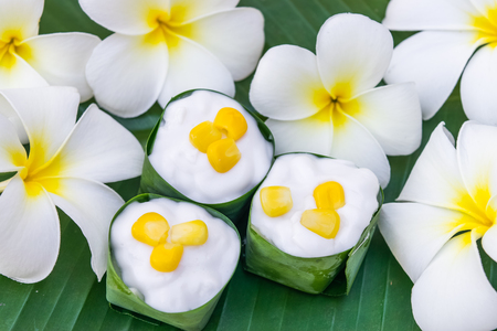 Thai coconut jelly in a pandan leaves cup with flower