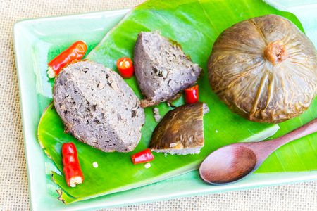 beef mum is a traditional food of the northeast in thailand. With banana leaves on wooden table Banco de Imagens