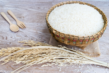 Thai jasmine rice in wooden bowl on wood background Stock Photo