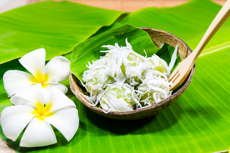 Coconut Ball (Thai Traditional Dessert) - Ka Nom Tom in a coconut shell with flowers on the banana leaf Stock Photo