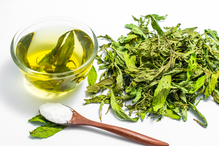 Dry stevia leaves with a glass cup stevia infusion on white background Stock fotó
