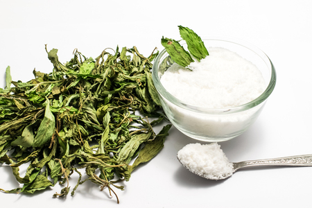 Dry stevia leaves and stevia powder in a glass
