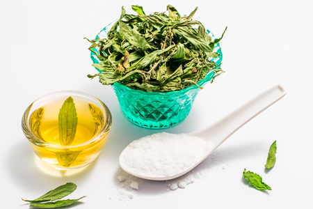 Dry stevia leaves in green glass on white background