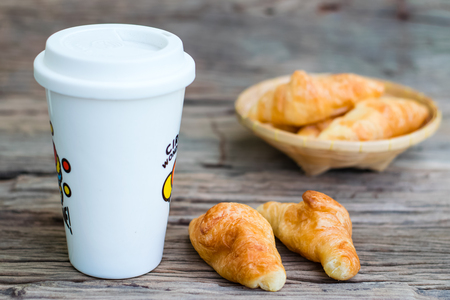 Fresh butter croissants with glass milk on old wood