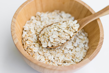 Oatmeal in wooden spoon, healthy diet breakfast.