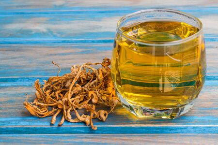 Dried cordyceps militaris mushroom brewed in a glass on the old wooden table Foto de archivo - 126792232