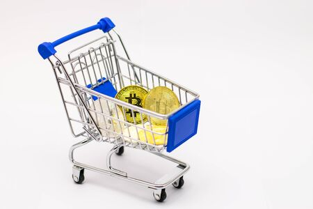 Bitcoin in mini Shopping Cart Isolated on White Background Foto de archivo - 127566153