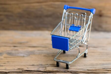 Shopping cart on an old wood background. Sale concept.