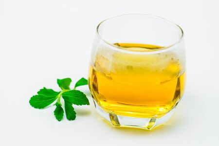 Stevia tea in a glass cup with fresh green stevia leaves on white background Stockfoto