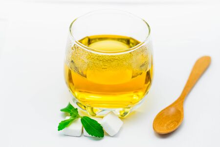 Stevia tea in a glass cup with fresh green stevia leaves and wooden spoon on white background Stockfoto