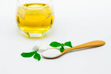 Stevia leaf and Stevia powder in a wooden spoon with Stevia tea in a glass cup Stockfoto