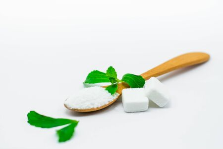 Stevia leaf with Stevia powder in a wooden spoon on white background