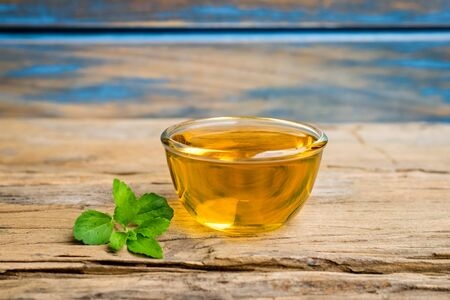 Stevia tea in a glass cup with fresh green stevia leaves on an old wood background.