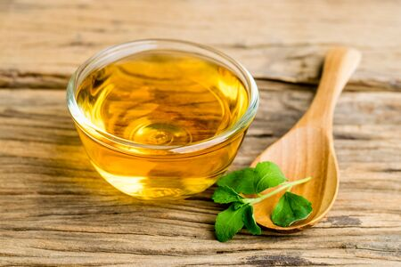 Stevia tea in a glass cup with fresh green stevia leaves and wooden spoon on an old wood background.