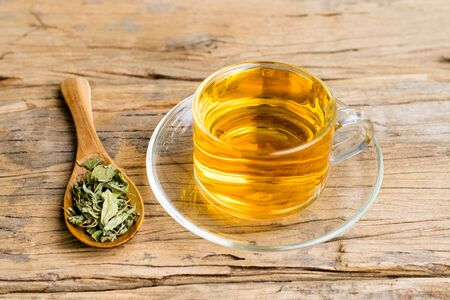 Stevia tea in a glass cup with Dry stevia leaves and wooden spoon on an old wood background.
