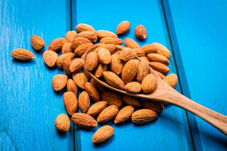Almonds with wooden spoon on blue wooden table