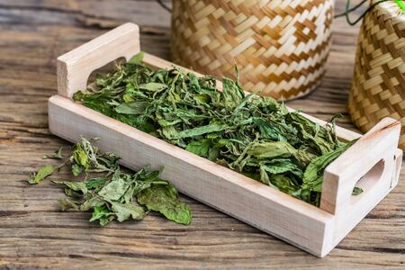 Dry stevia leaf in a wooden tray on an old wooden floor