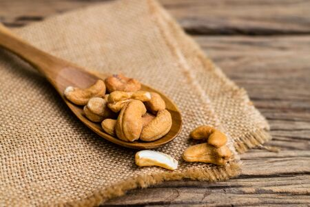 Roasted Cashews in wooden spoon on old wood
