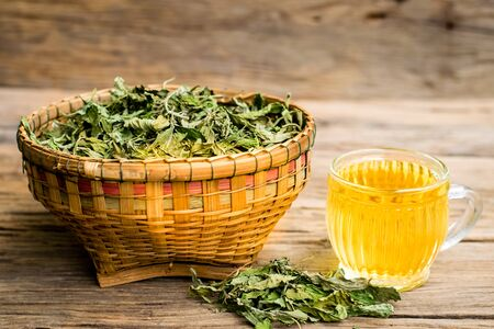 Dry stevia leaf in the basket with stevia tea in a glass cup on an old wooden floor Zdjęcie Seryjne