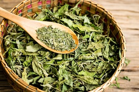 Dry stevia leaf in the basket with wooden spoon on an old wooden floor Zdjęcie Seryjne