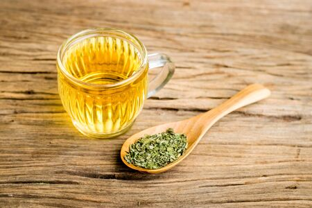 Stevia tea in a glass cup with dry stevia leaf in wooden spoon on an old wooden floor Zdjęcie Seryjne