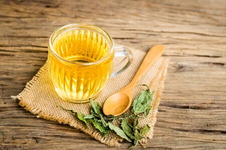 Stevia tea in a glass cup with dry stevia leaf on an old wooden floor