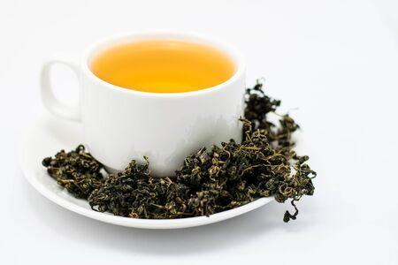 Dry gynostemma pentaphyllum leaf with tea brewed in a white cup on white blackground Standard-Bild
