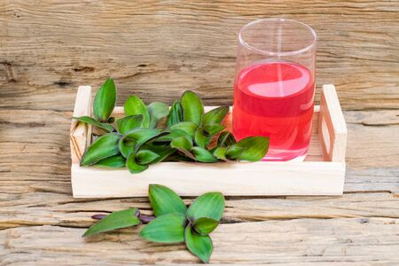 river spiderwort juice in a glass and river spiderwort leaf have medicinal properties on the old wooden table