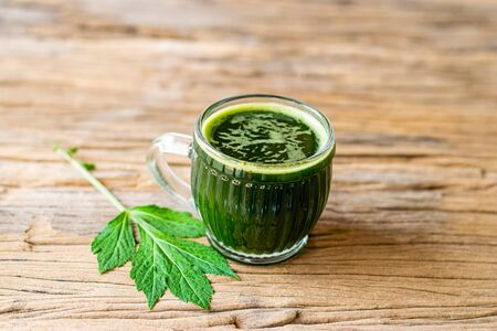 Herbal juice of white mugwort high medicinal benefits in a glass on an old wooden table.