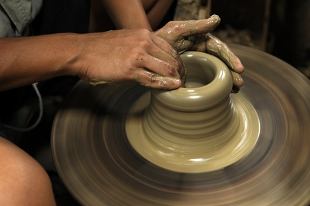 Artist shaping a bowl on a pottery wheel  photo