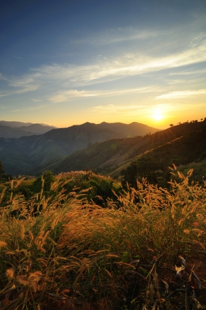 Sunsets over mountains and grass Stock Photo