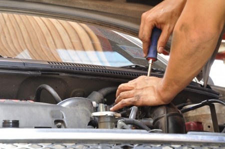 Mechanic doing unscrew the ignition plugs of a car