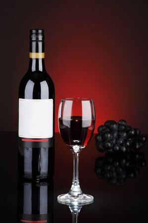 Still-life with bottle and glass of wine over red background  Stock Photo